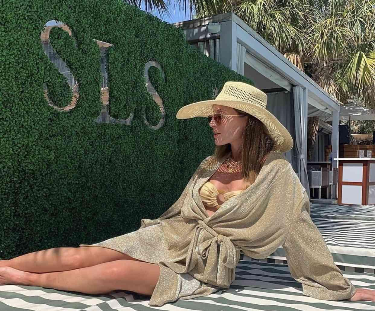 Woman lounging in front of SLS sign