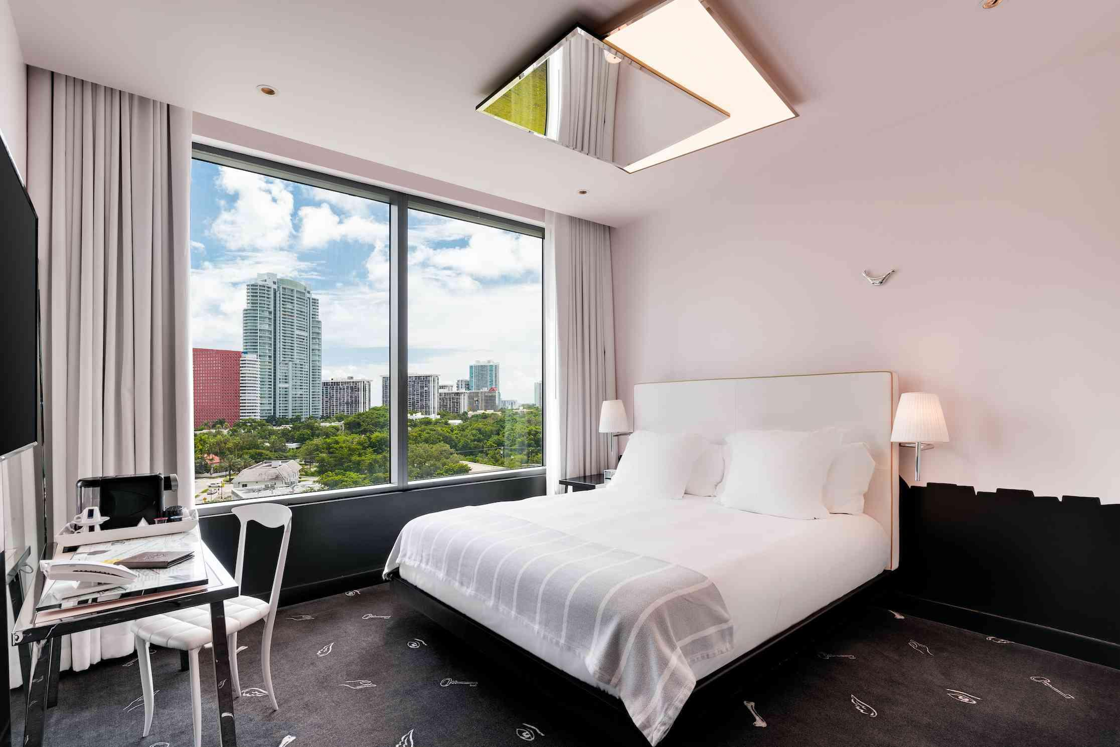 king bed in room with high ceilings and city views