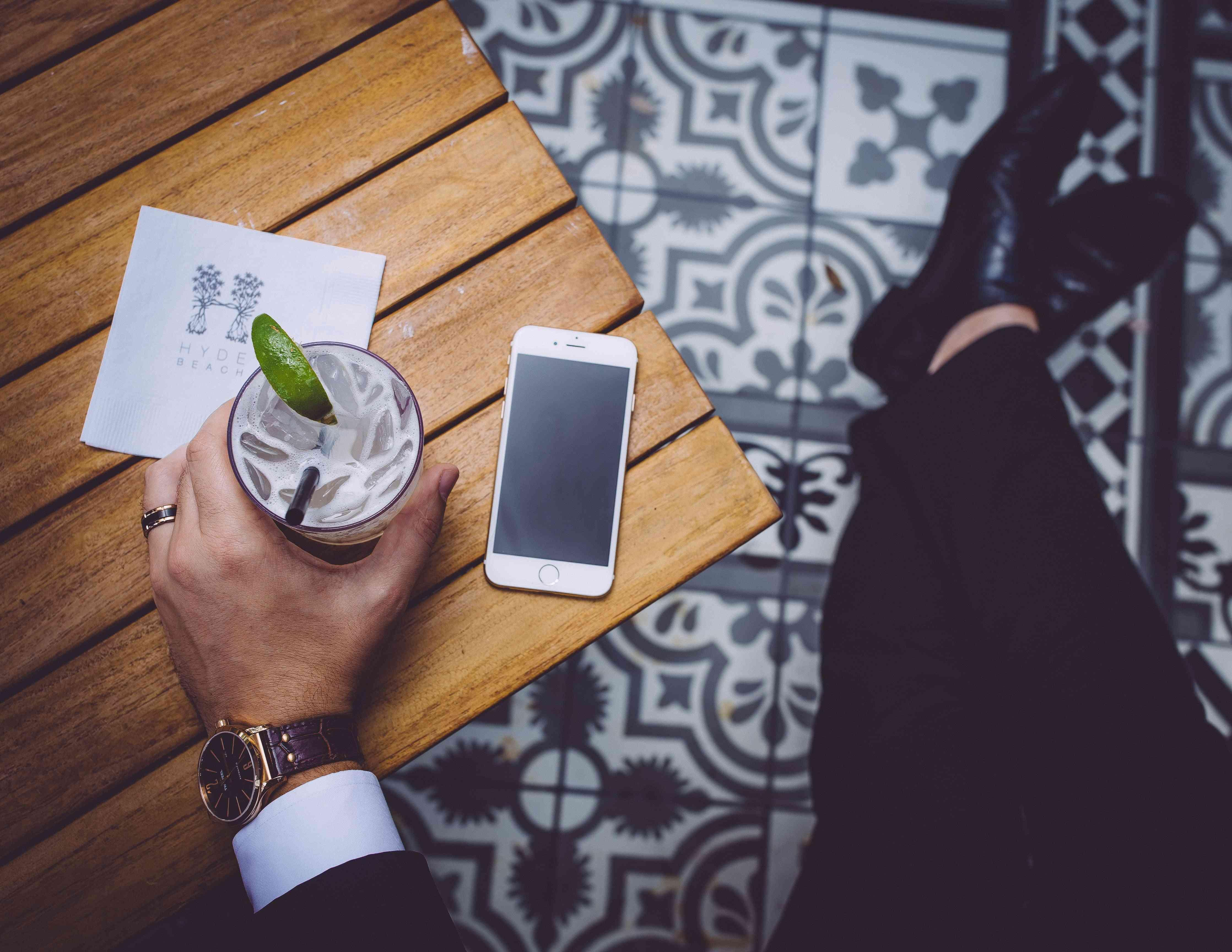 man holding cocktail with phone on table