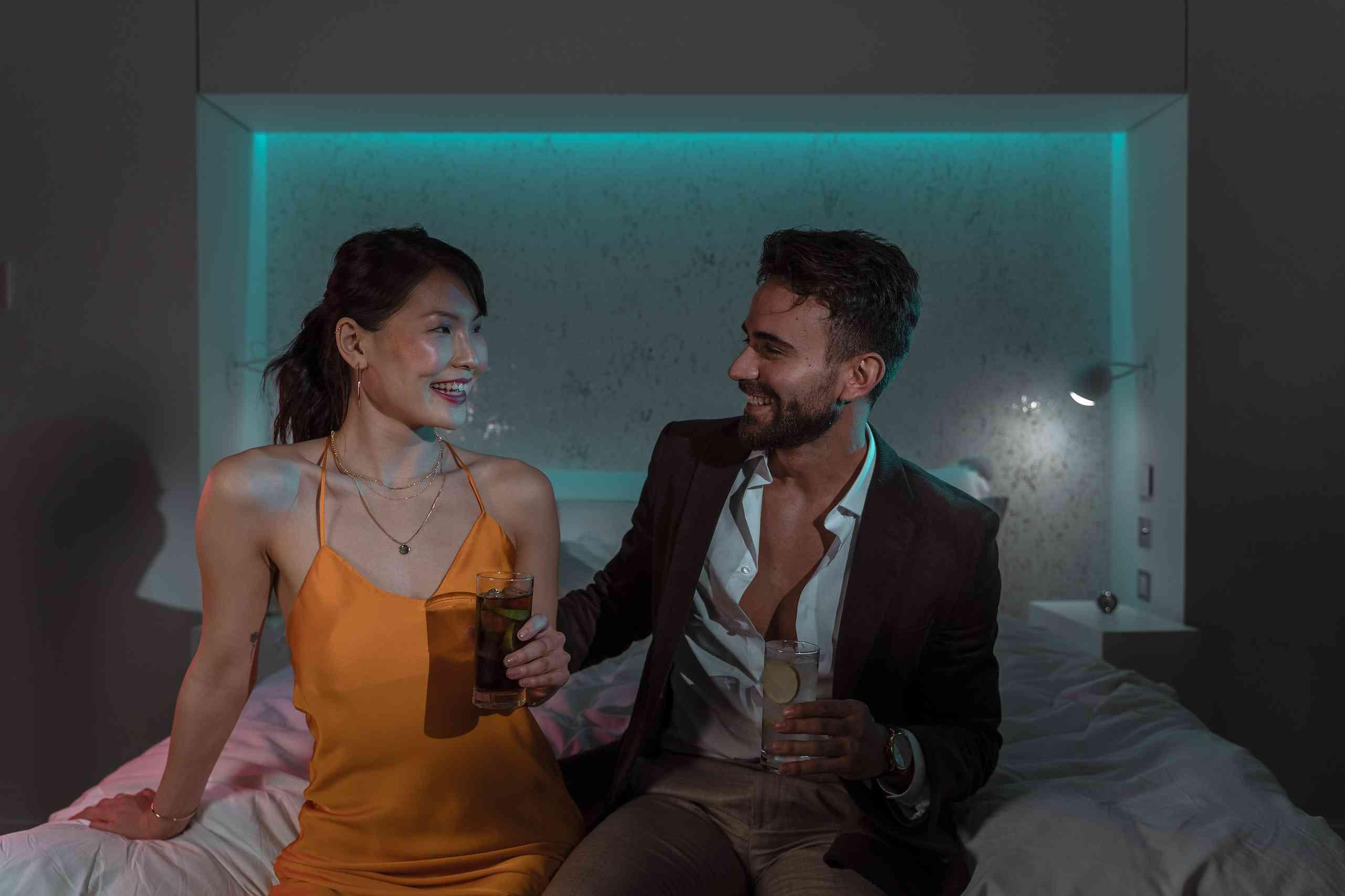 man and woman have drinks on bed