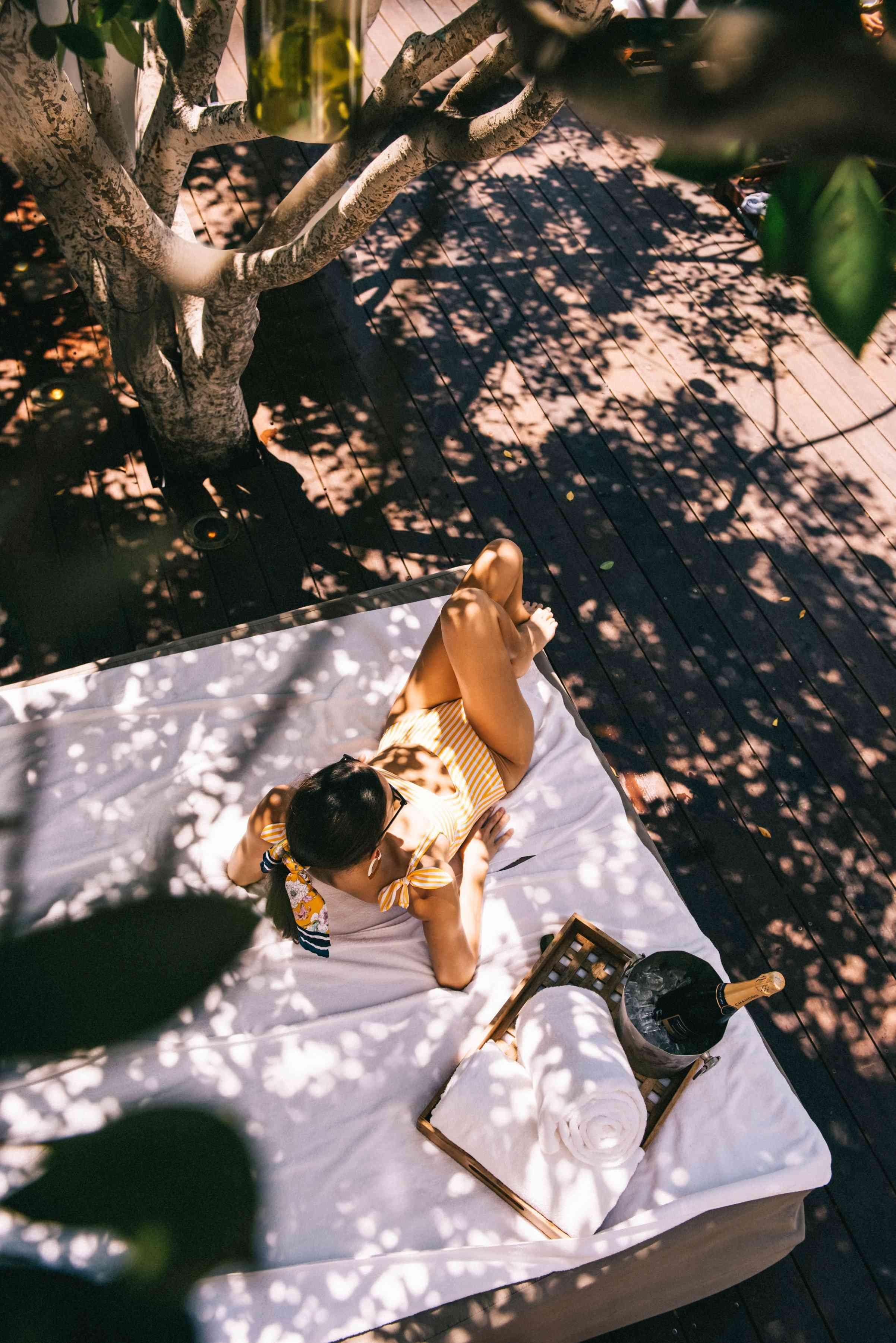 woman on a blanket outside with champagne