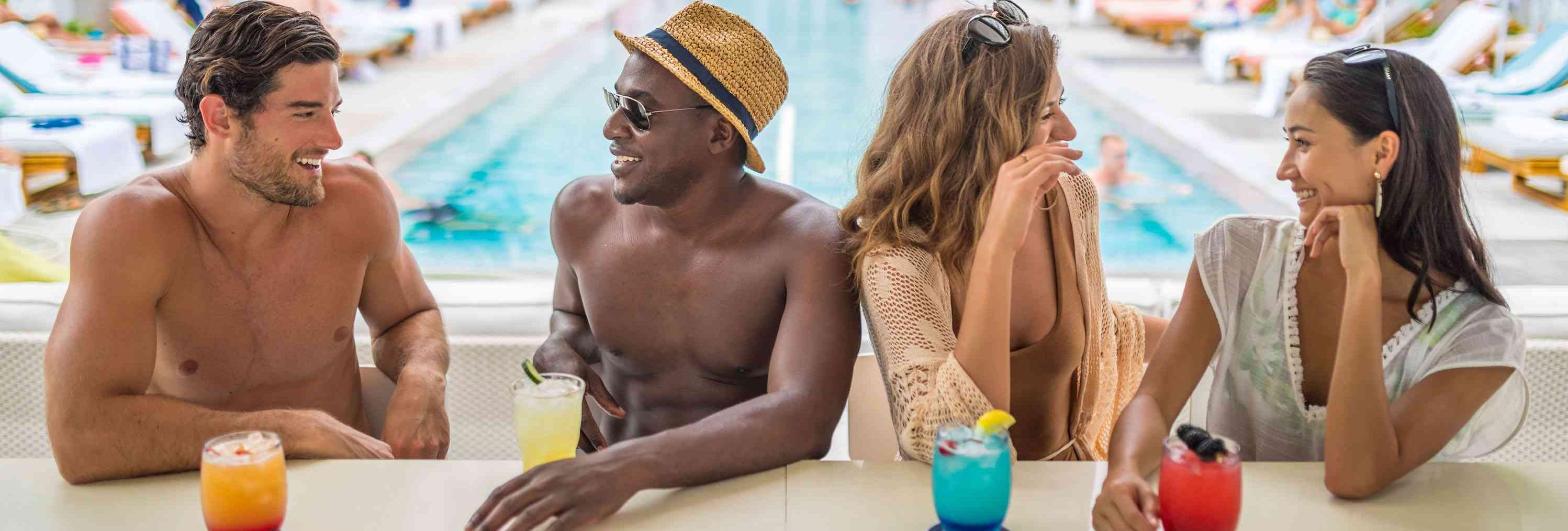 four people at a pool with drink outside