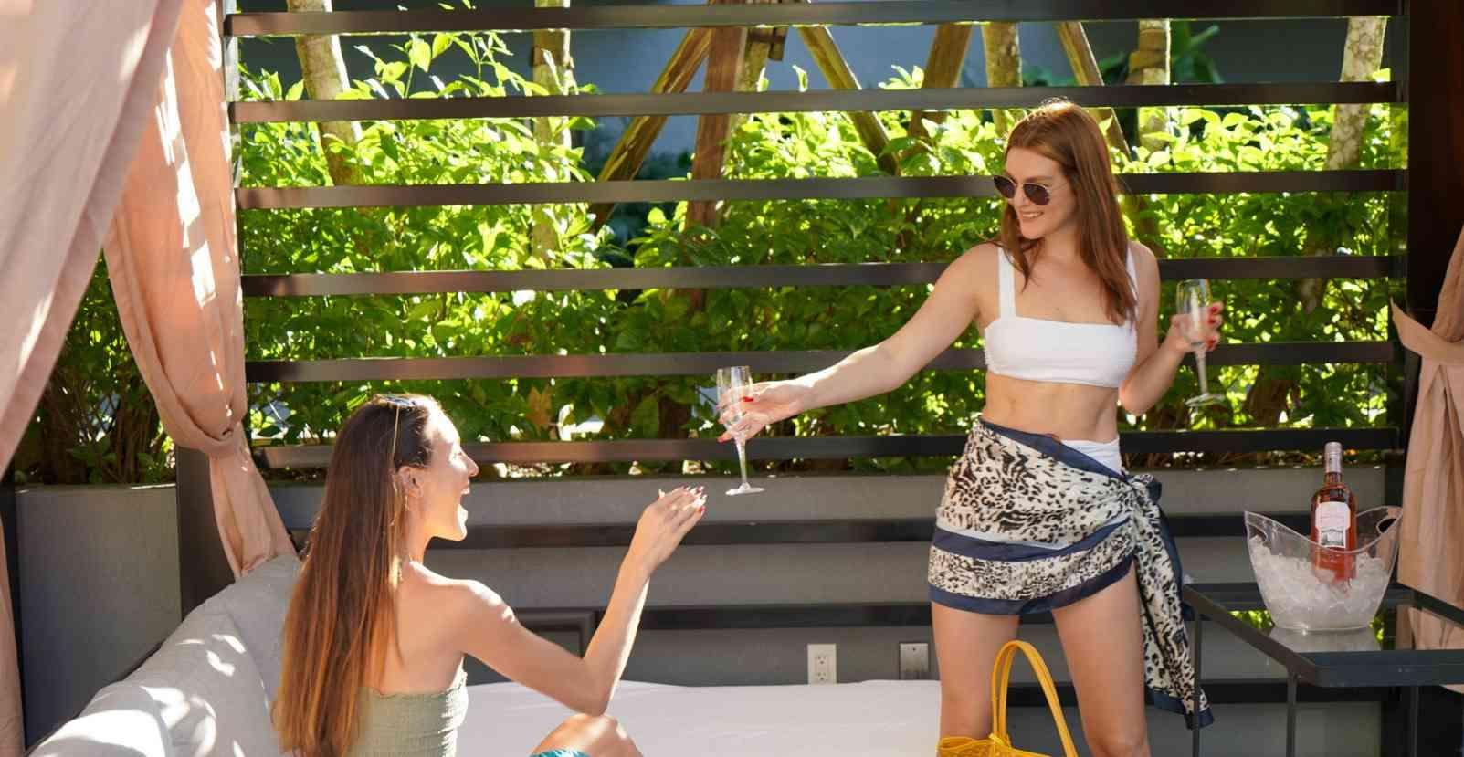 two women with champagne at a cabana
