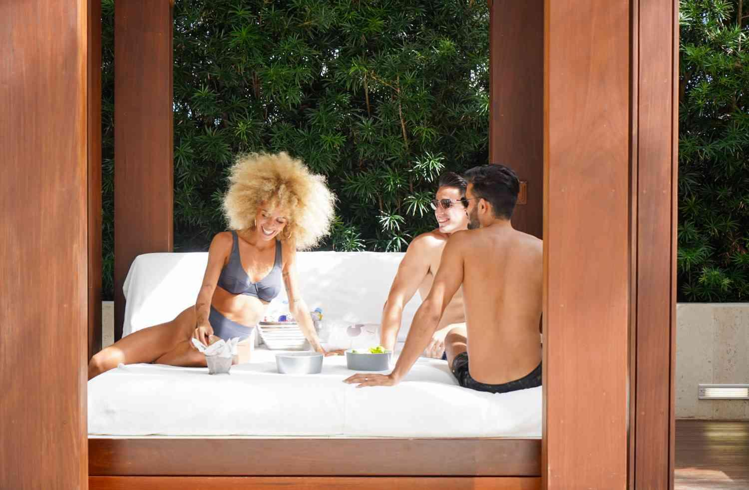 three people at a pool cabana