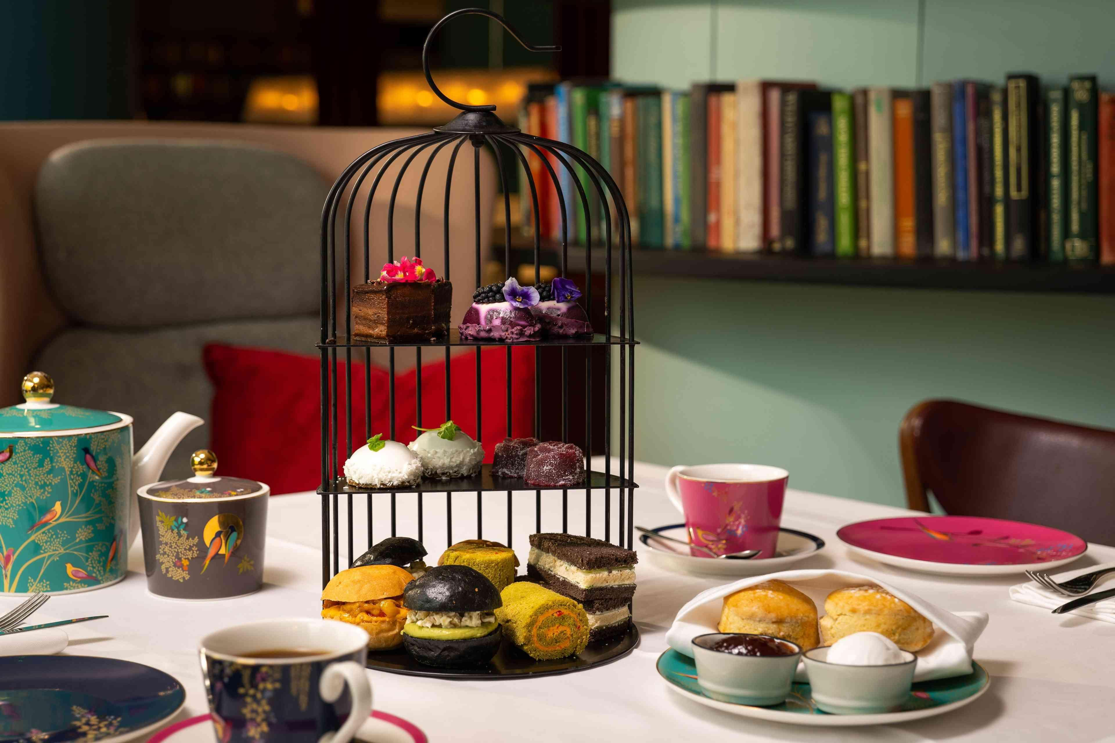 Desserts displayed in black cage on table with tea cups