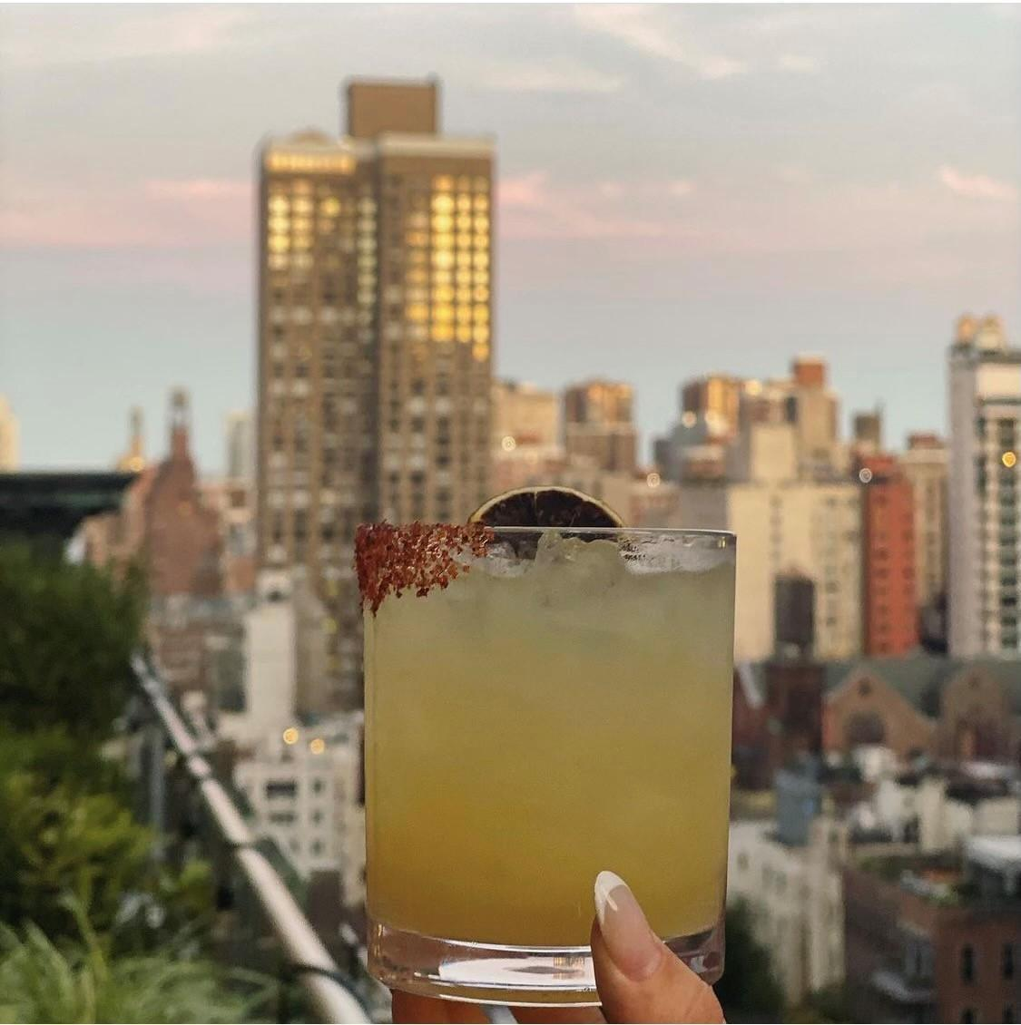 toasting a cocktail with the NY skyline behind it