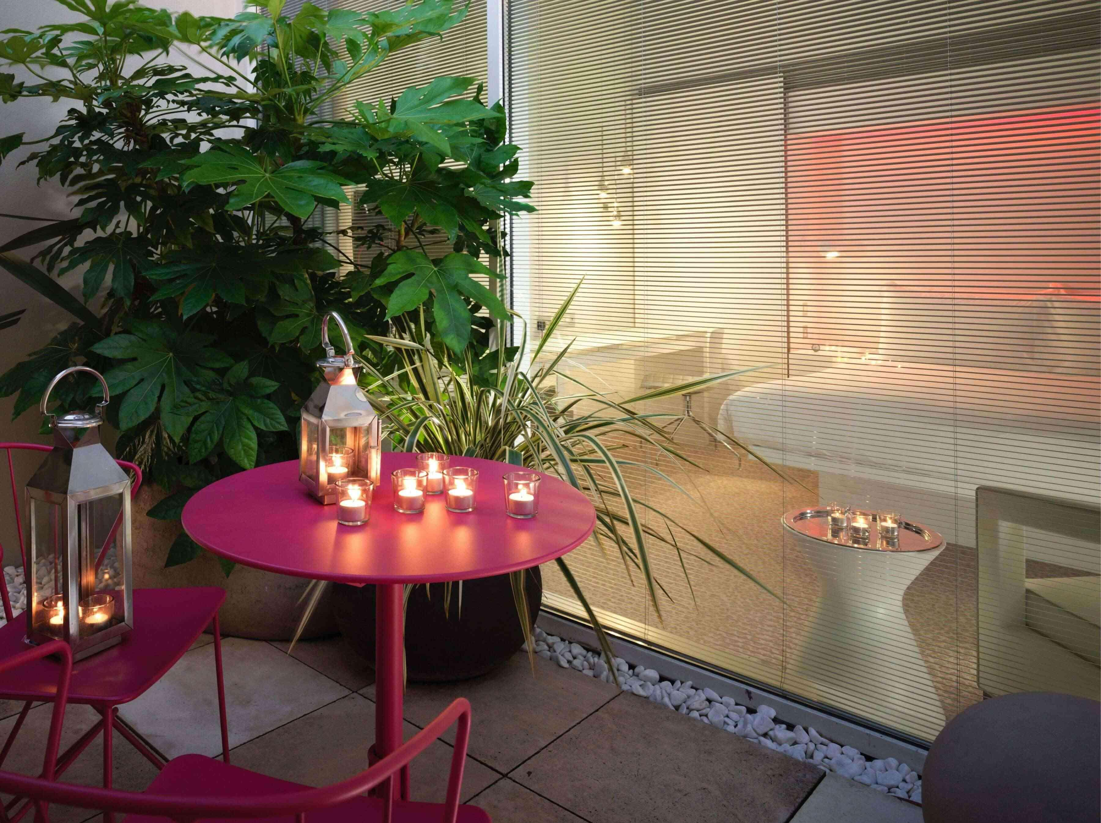 Bright pink table with candles next to a plant with a bedroom in the background