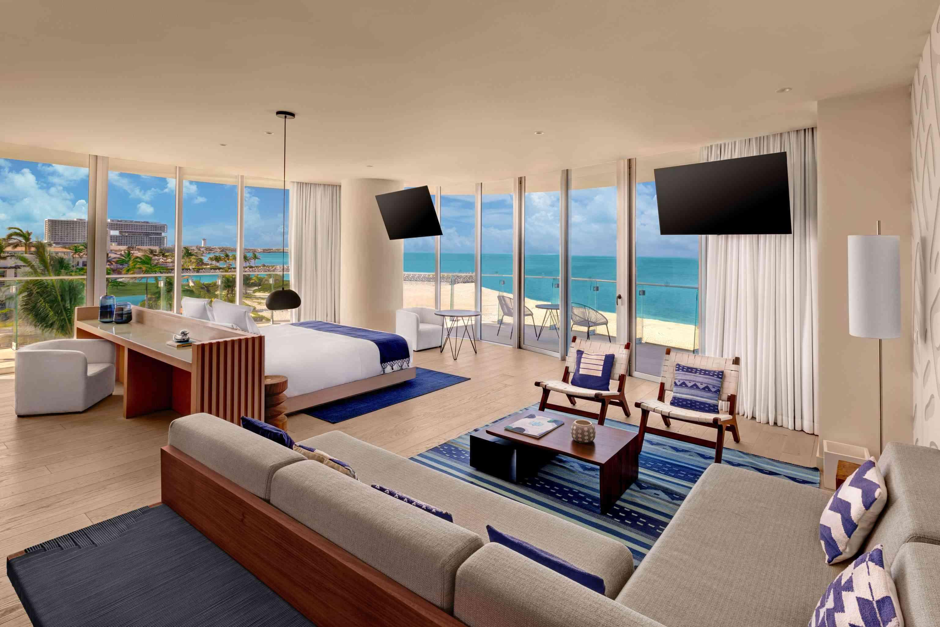 Wide shot of the Premier Ocean Front One Bedroom Suite that includes a desk, a large seating area, 2 televisions, a bed, and a balcony with a view of the ocean