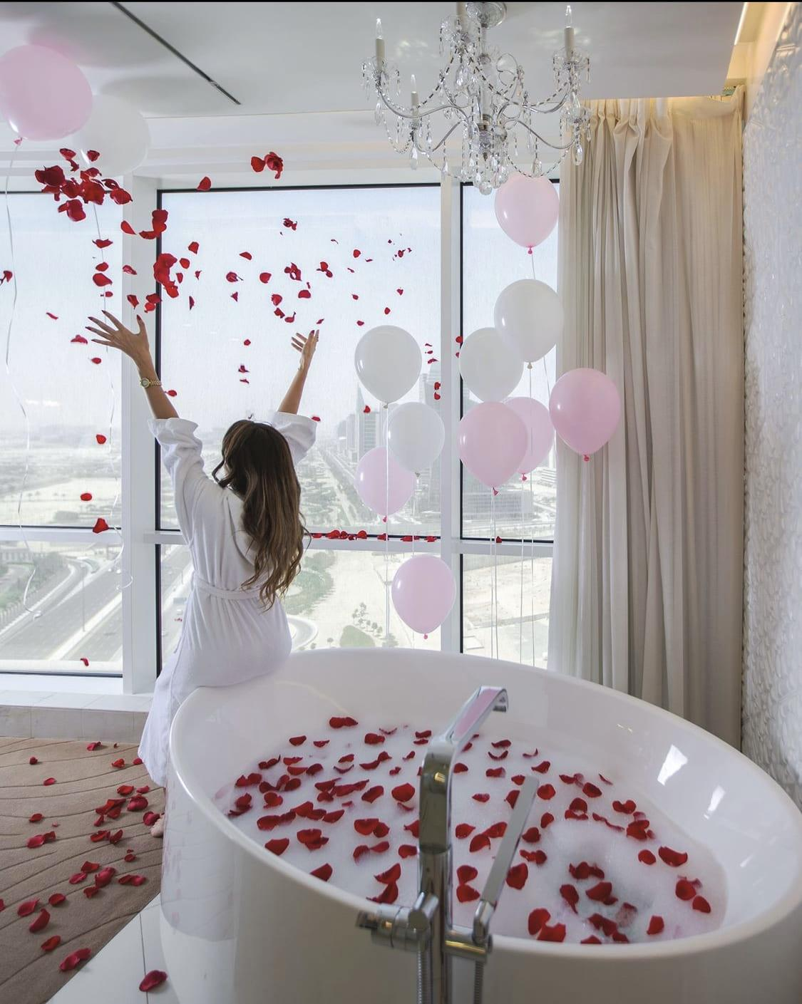 Woman throwing rose petals while leaning on a bathtub filled with rose petals